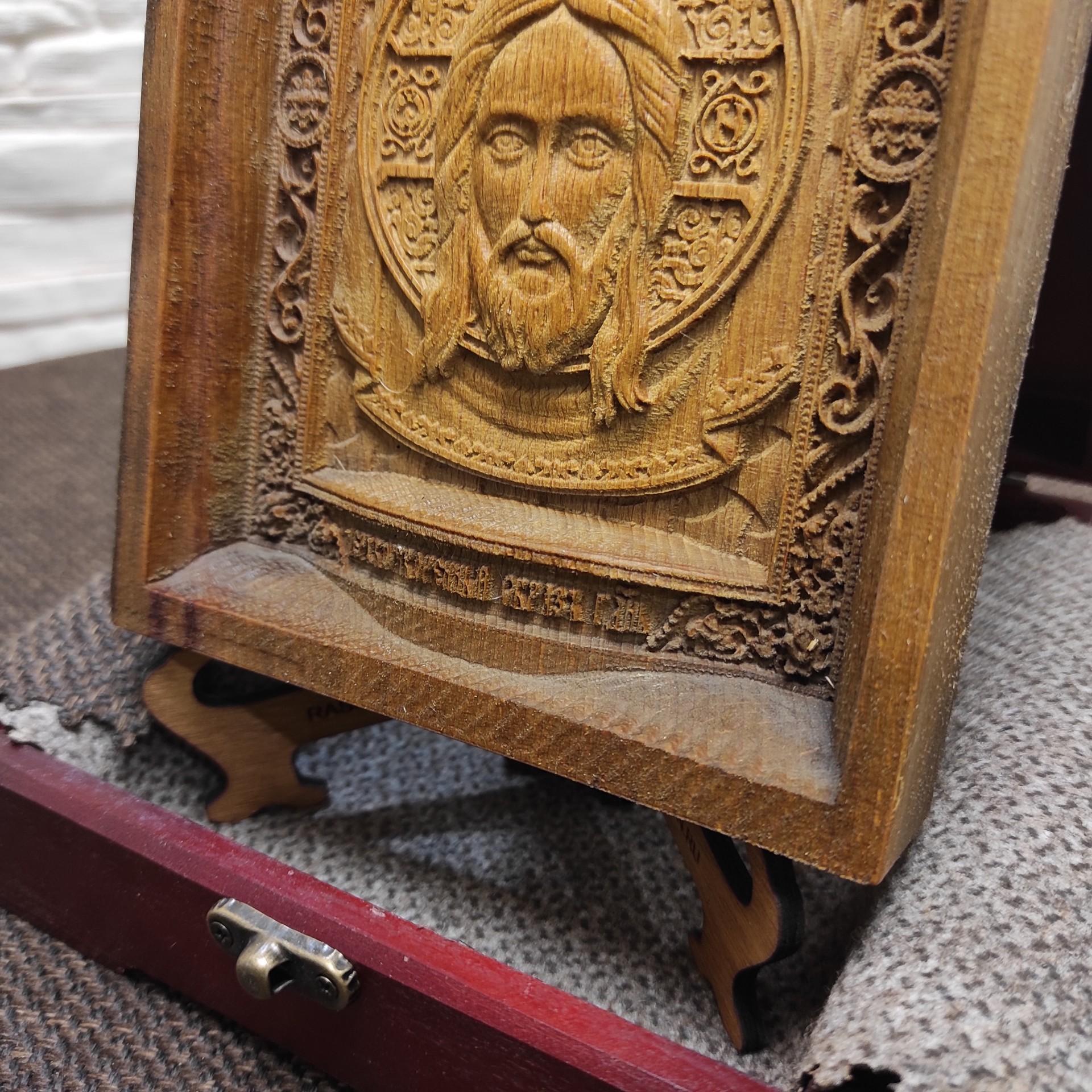 Фото нижней части маленькой резной иконы Спас Нерукотворный уложенной на подставке в футляре с покровом