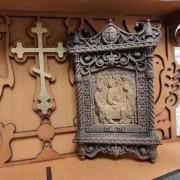 Фото маленькая резная икона святой Троицы вид на полочке