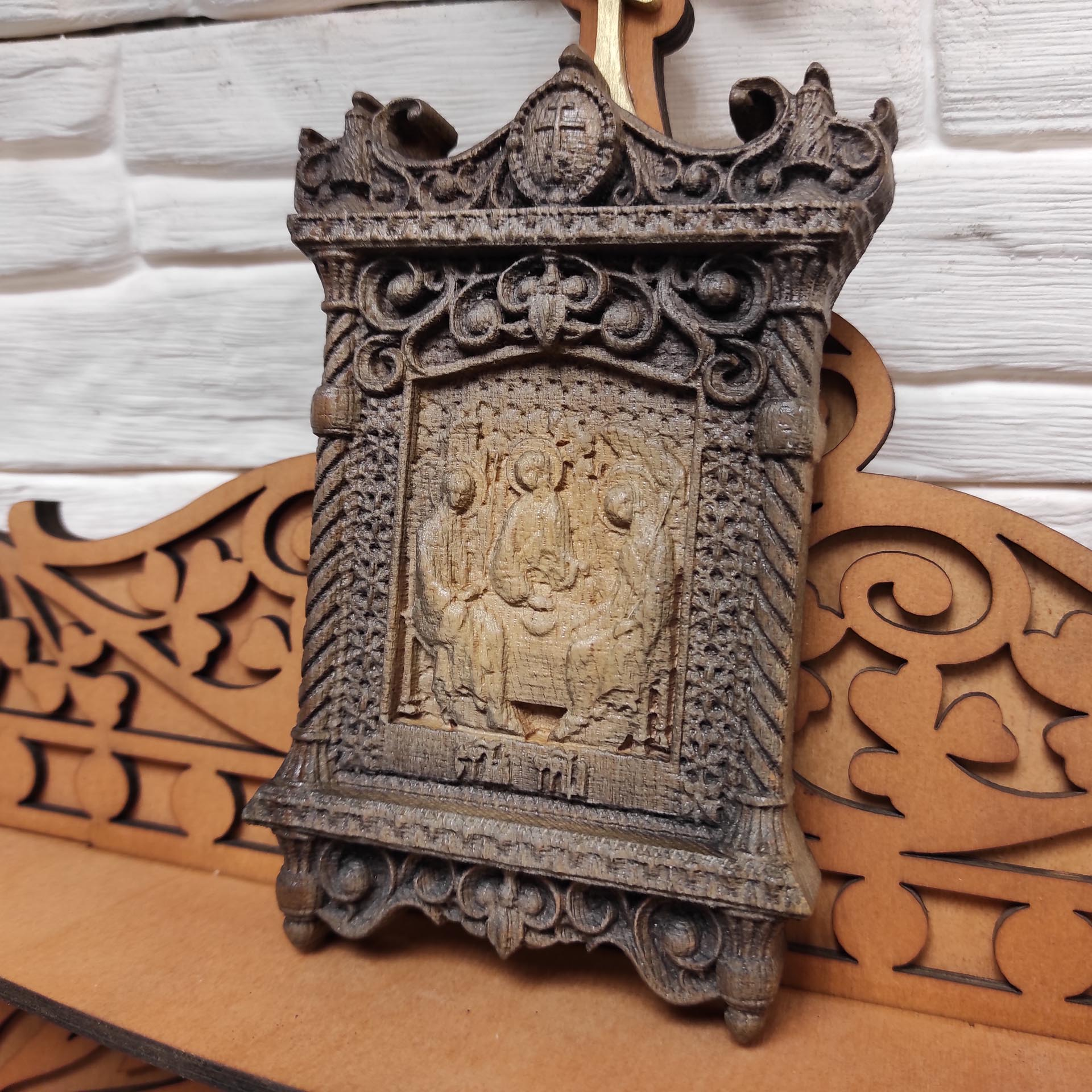 Фото маленькая резная икона святой Троицы вид на полке